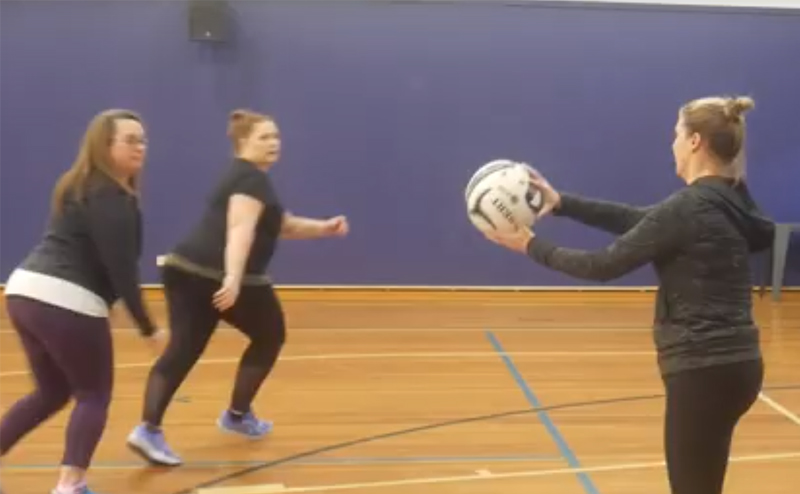 Women playing netball together