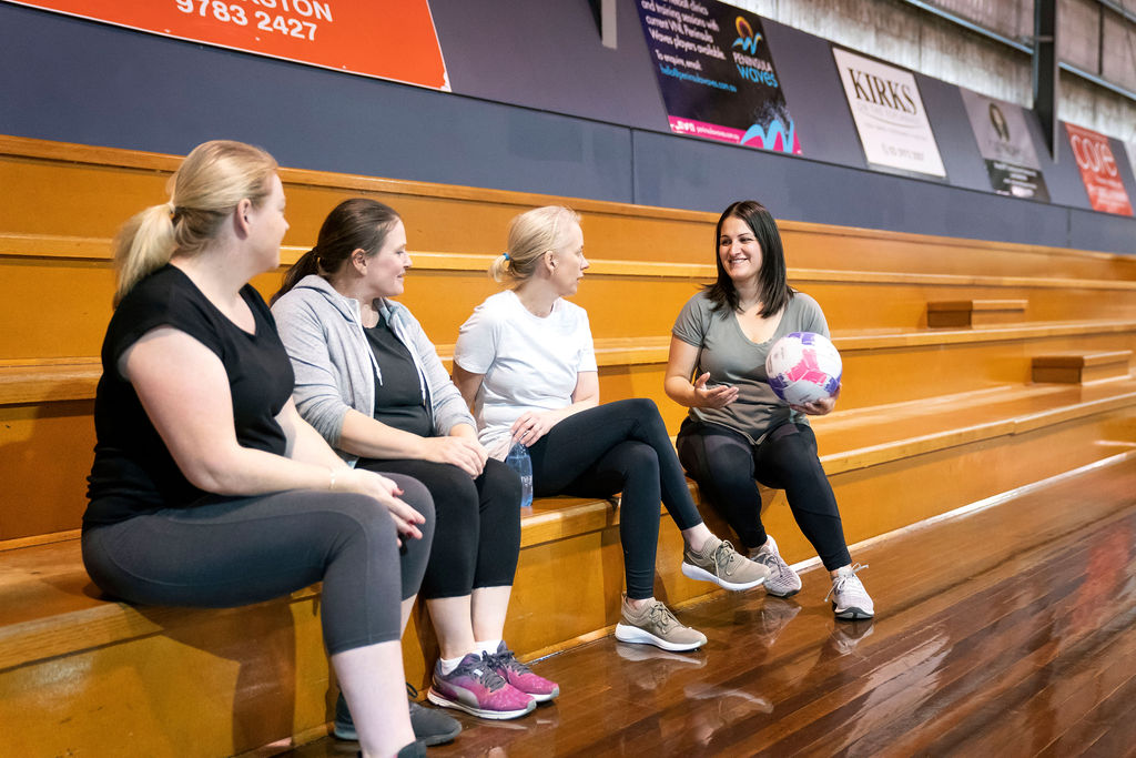 This Girl Can - Victoria ambassador Kelly sitting with teammates on the netball grandstand